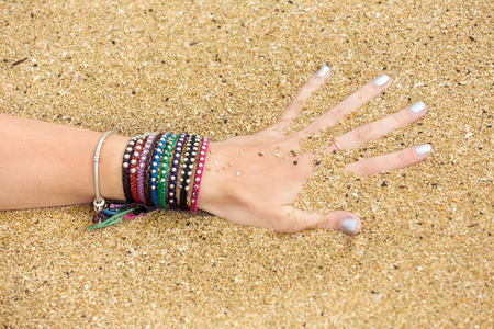 percolate: Female hand with bracelets  in the ocean water, playing with sand