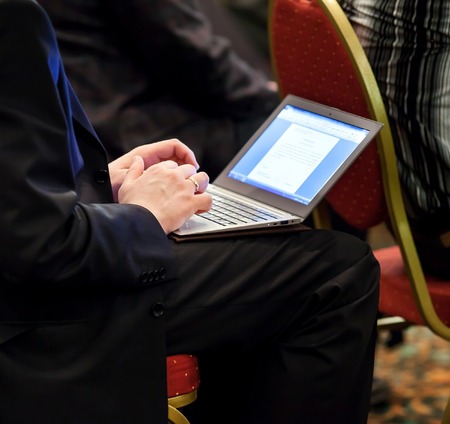 ultrabook: Businessman on a conference with ultrabook on his knees makes important notes Stock Photo