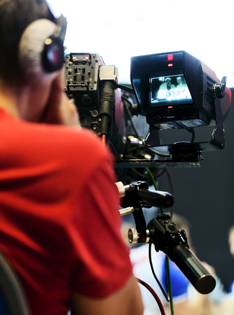 camera operator: Professional cameraman with headphones with HD camcorder in live television