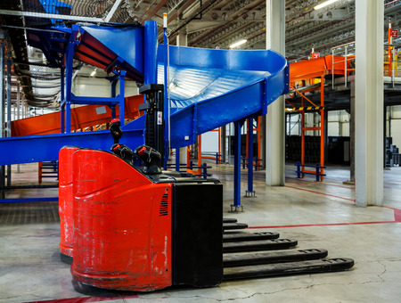 forklifts: Sorting line for cargo in large modern warehouse with forklifts