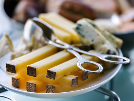 sliced cheese: Sliced ??durum cheese on a plate and special  cutlery to capture cheese. Soft focus