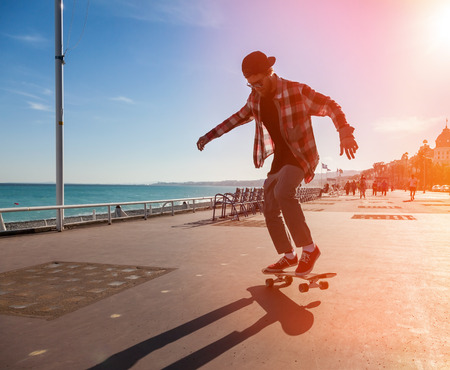 promenade: Silhouette of Skateboarder jumping in city on background of promenade and sea Stock Photo