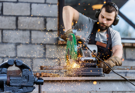Industrielle métallique de coupe des travailleurs avec de nombreux étincelles vives travailler sur Scie à onglets avec lame circulaire Banque d'images