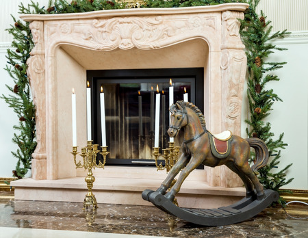 fireplace christmas: Old wooden rocking horse for children on the background of burning candlesticks in sconces near the fireplace