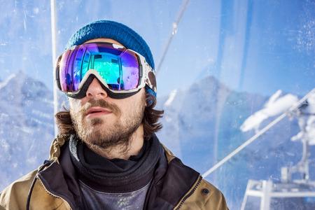 hombre con barba: Retrato de hombre joven con barba en la máscara de gafas de sol, se eleva a la cima en teleférico de cabina de pasajeros desde la estación de esquí en el fondo de las montañas y el cielo azul
