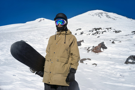 elbrus: Portrait of snowboarder on background beautiful landscape of snowy high mountains Elbrus standing with snowboard
