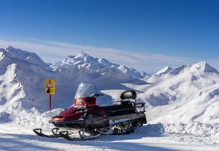elbrus: Snowmobile stands on the background high mountains Elbrus Stock Photo