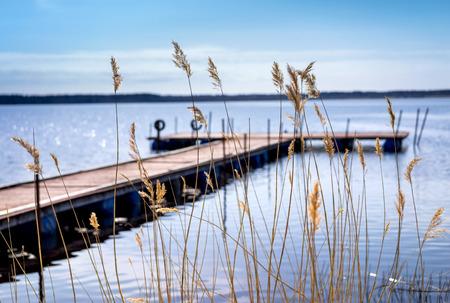 Pier zum Vergnügen und Fischerboote am Ufer des Ladoga-See in Karelien. Weicher Fokus. Im Vordergrund der hohen Gras Standard-Bild - 38068672