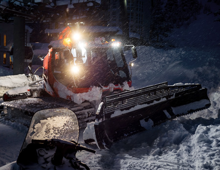 snow grooming machine: Snowcat preparing a slope at night in high mountains at skiing resort of the North Caucasus Elbrus Stock Photo