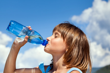 girl glasses: Attractive young beautiful girl drinking water from plastic bottles