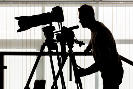 Silhouette of photographer and cameraman shot the video on a tripod at the workplace indoors Banco de Imagens