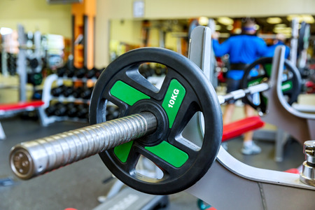 man working out: Barbell holder in the gym. On the rear background man, working out with barbell Stock Photo