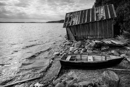 barn black and white: Old wooden fishing boat and barn on lake coast in Karelia. Black and white photo Stock Photo