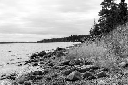 ladoga: Beautiful landscape on shores of Lake Ladoga in Karelia. Moored near the shore fishing boat. Black and white photo
