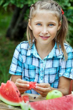 cute teen girl: Молодая красивая девушка, едят вкусную спелый арбуз в саду