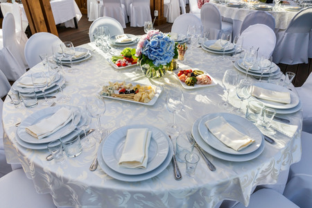 Elegant banquet tables prepared for a conference or a party and covered with a white tablecloth and decorated with flowers for guests Stock Photo