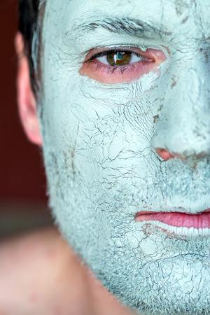 Mannen gezicht close-up op het gezicht blauwe klei masker. Behandeling en zorg voor het gezicht huid Stockfoto