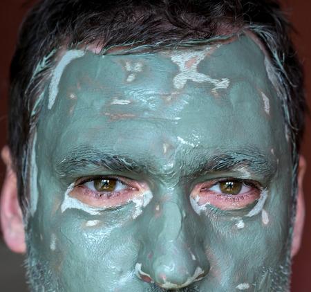 Männer Gesicht Großansicht auf blauem Ton Gesichtsmaske. Behandlung und Pflege für die Gesichtshaut Standard-Bild - 40163064