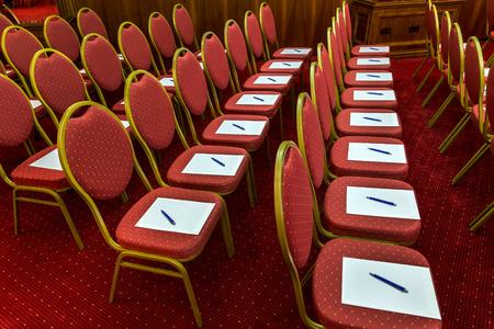 ビジネス会議の前に空の企業会議室で椅子に議題にはペンとメモ帳