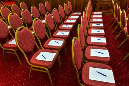 Notepad with pen for agenda on chairs in empty corporate conference room before business meeting