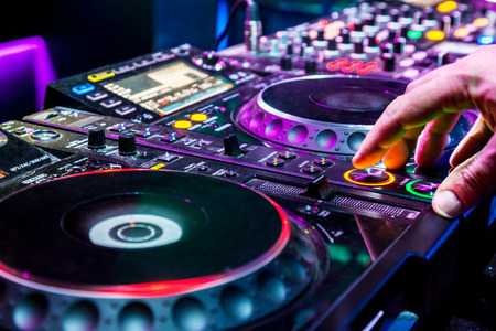 Dj mixes the track in the nightclub at party