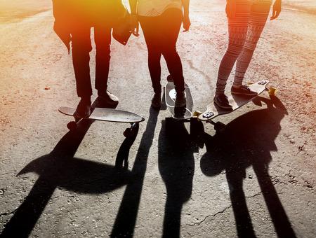 juventud: Silueta de tres amigos skaters en el skatepark. Parte inferior de los cuerpo dos niñas y un tipo de longboard y skate Foto de archivo