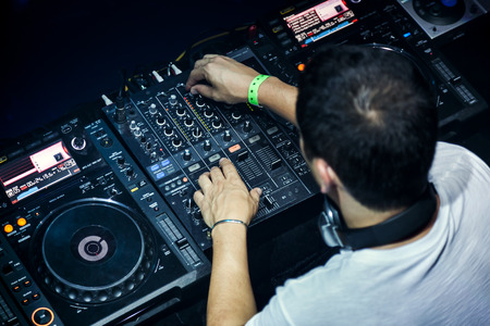 Dj in headphones mixes the track in the nightclub at party Banco de Imagens