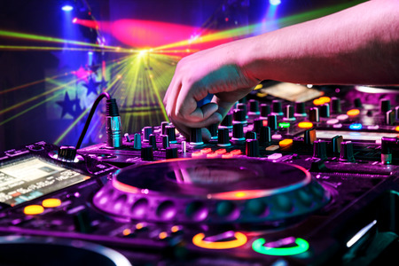 audio mixer: Dj mixes the track in the nightclub at party. In the background laser light show