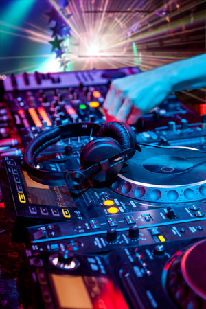 Dj mixes the track in the nightclub at party. In the background laser light show. Headphones in foreground and DJ hands in motion