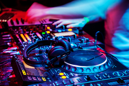 Dj mixes the track in the nightclub at party. Headphones in foreground and DJ hands in motion photo