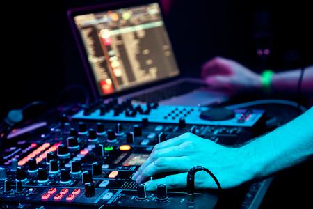 musica electronica: DJ mezcla la pista en el club nocturno en la fiesta Foto de archivo
