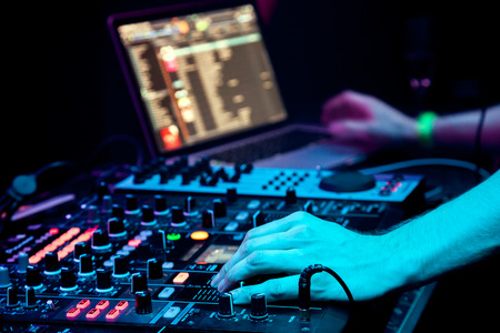 dj: Dj mixes the track in the nightclub at party