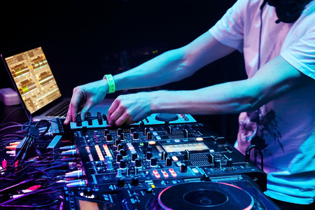 Dj mixes the track in the nightclub at party. Headphones in foreground and DJ hands in motion