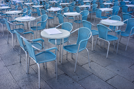 pavement: Metal tables and chairs in a cafe on the street