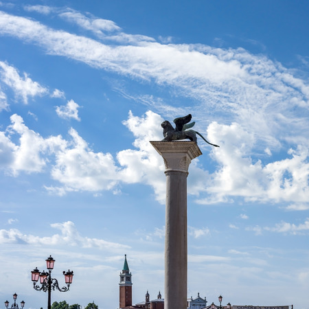winged lion: VENICE, ITALY - JULY 2,2014: Silhouette of east column of St. Mark (bronze statue of winged lion) on Piazza San Marco in Venice, Italy