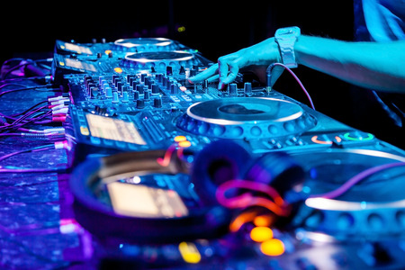 dj turntable: Dj mixes the track in the nightclub at party. Headphones in foreground and DJ hands in motion
