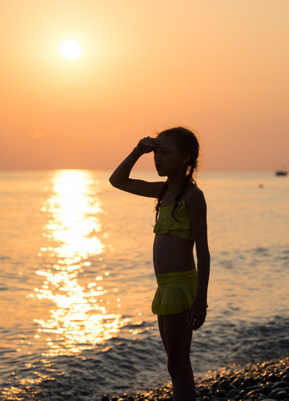 beach girl: Young girl stand on shore sea and looking off into the distance with his hand raised to his forehead at sunset. Beautiful landscape
