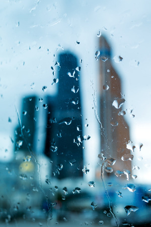big behind: Silhouettes of big towers of the business center behind the wet glass, where on the street cloudy and rain