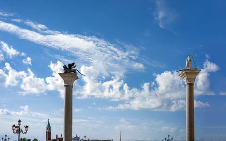 piazza san marco: VENICE, ITALY - JULY 2,2014: Silhouettes Columns of St. Mark (bronze statue of winged lion) and St. Theodore, marble sculpture depicting warrior Theodore of Tyrone on Piazza San Marco in Venice, Italy Editorial