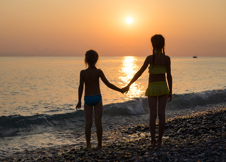 rear view girl: Silhouette of two young girls sisters on the sea beach holding hands and looking into distance. Beautiful landscape at sunset Stock Photo