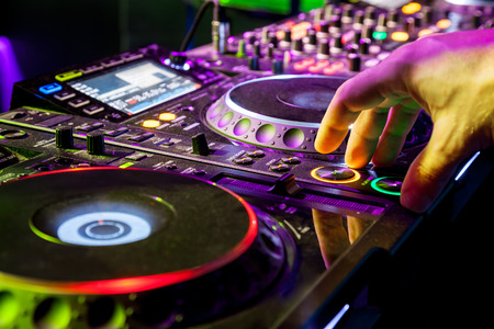 mixing: Dj mixes the track in the nightclub at party