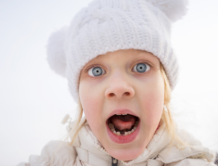 fear child: Portrait of very frightened young girl screaming in open air, in state of shock Stock Photo