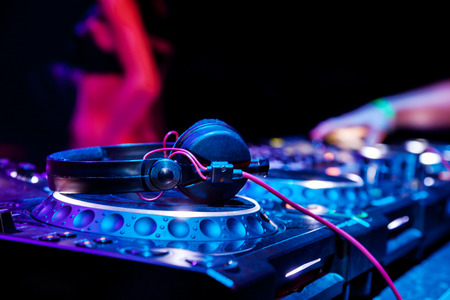 audio mixer: Dj mixes the track in the nightclub at party. Headphones in foreground and DJ hands in motion