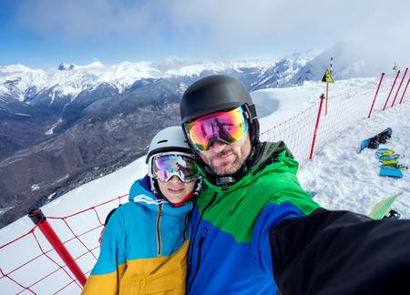 幸せなカップルのスノーボーダー山頂の端に立って、スキーで雪山の背景にカメラやスマート フォンの selfie 肖像画