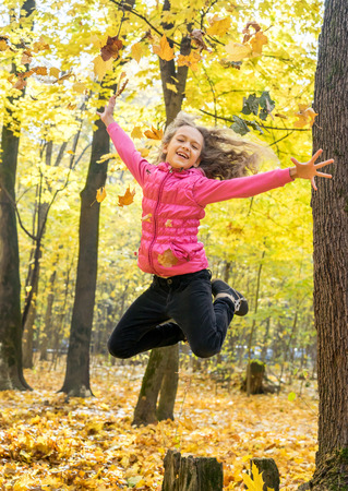 leafage: Happy beautiful young girl throw up autumnal leafage and high jump in the autumn forest park
