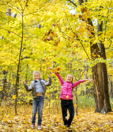 blond girl: Happy beautiful little children throw up autumnal leafage in park Stock Photo