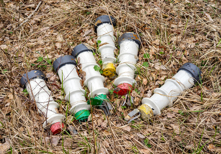 resistivity: Industrial old ceramic high voltage insulators lying in dry grass Stock Photo