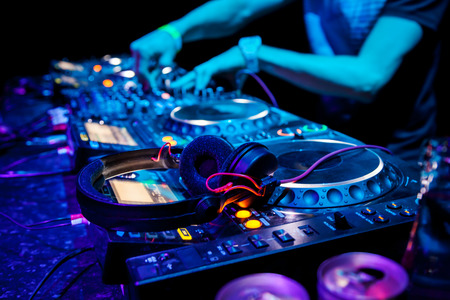 dj: Dj mixes the track in the nightclub at party. Headphones in foreground and DJ hands in motion