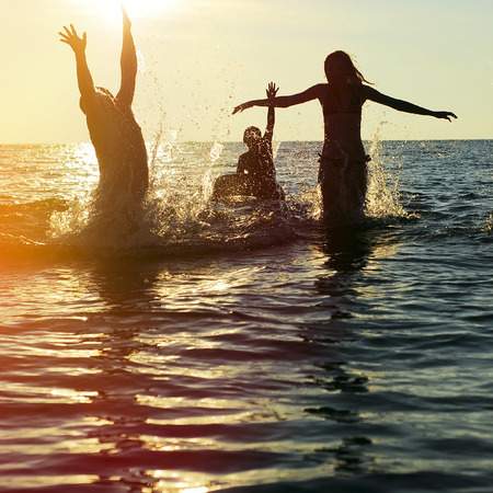 water splashing: Silhouettes of young group of people jumping in ocean at sunset