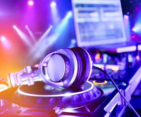 party dj: Mezclador de DJ con los auriculares en el club nocturno. En el fondo espectáculo de luces láser